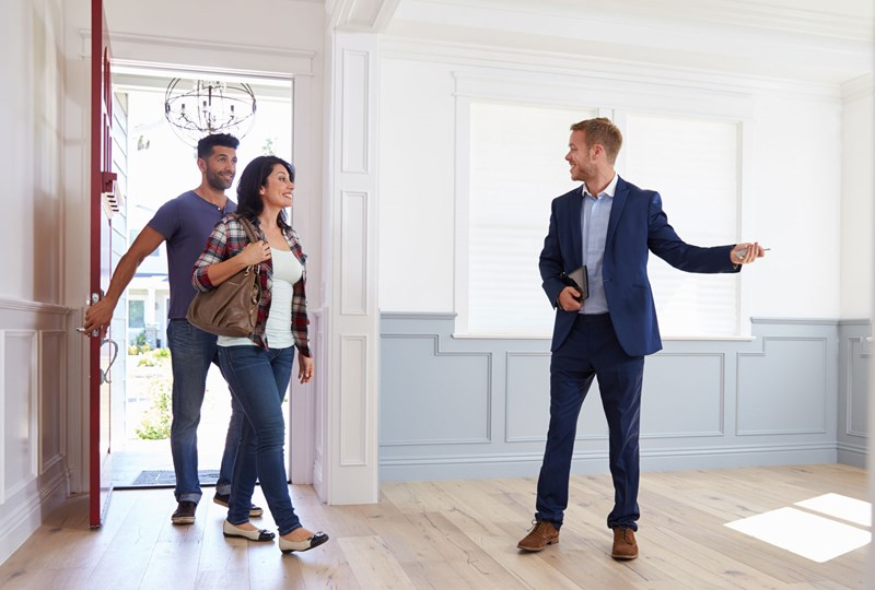 real estate agent showing a couple a home