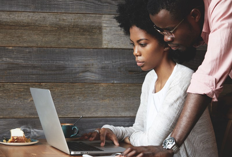 man and woman browsing on a laptop