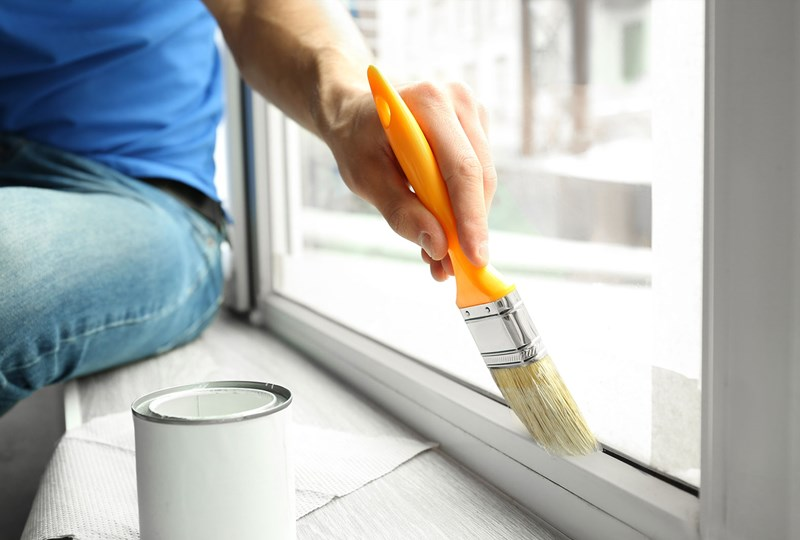 Person painting interior of home window