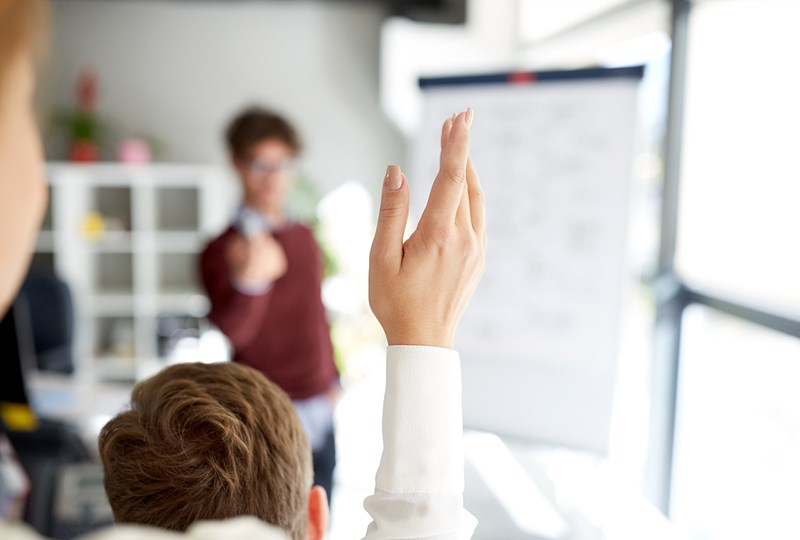 woman raising her hand to ask a question
