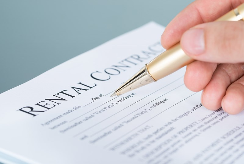 person signing a rental contract